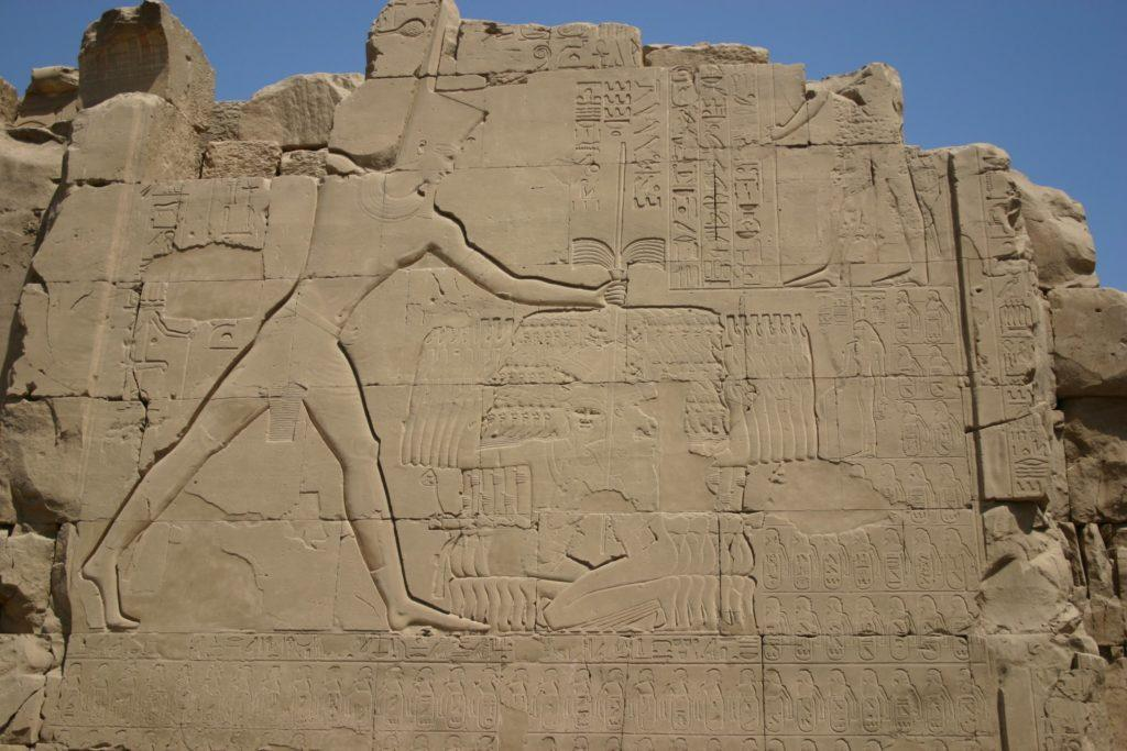 "Thutmose ""III"" smiting his enemies, on the seventh pylon at Karnak."